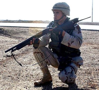 A soldier kneeling with a shotgun