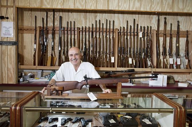 Portrait of a happy gun shop owner